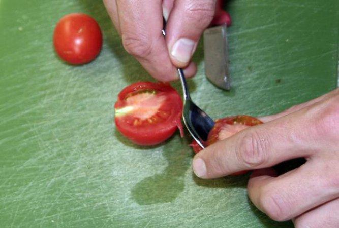 Mit einem Löffel das glibbrige Tomatenmark samt Kernen heraustrennen